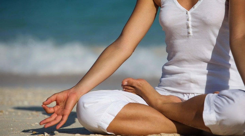 monaco-service-caucasian-woman-practicing-yoga-at-seashore-min
